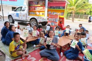 写真: 自分が作ったものを見せる子供たち。後ろには移動図書館車両はるの号