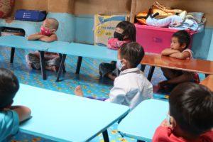 写真: 図書館スタッフのブンちゃんの読み聞かせに聞き入る小さい子供たち