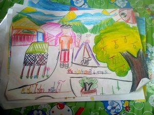 子供たちがおりの並んだ動物園にいて、ブランコや実を付けたマンゴーの木もある