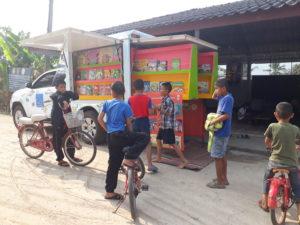 写真: ピックアップトラックを改造した図書館カーはるの号とその周りに集まる子供たち