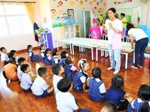 P Cha explaining mobile library activity to group of children